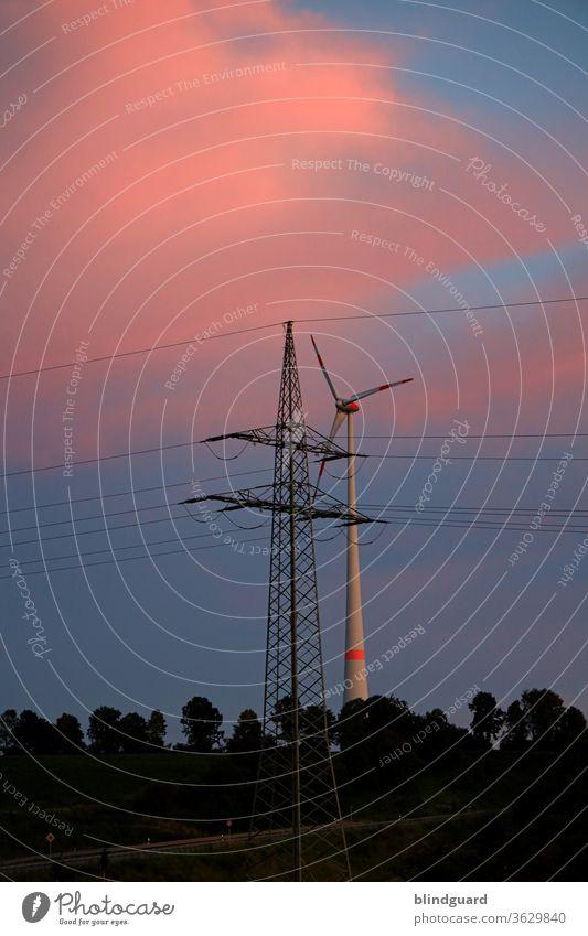 Energiemix. Windrad hinter einem Mast der Überlandleitung für die bundesweite Stromversorgung, mit Wald vor einem abendlich rot-blauen Himmel. Energiewirtschaft