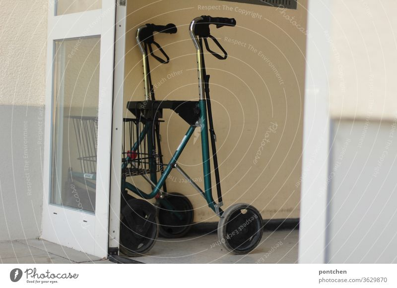 Ein Rollator steht im Hauseingang eines Mehrfamilienhauses. Gehhilfe, Altern. gehhilfe altern hauseingang tür offen mehrfamilienhaus Senior Gesundheit