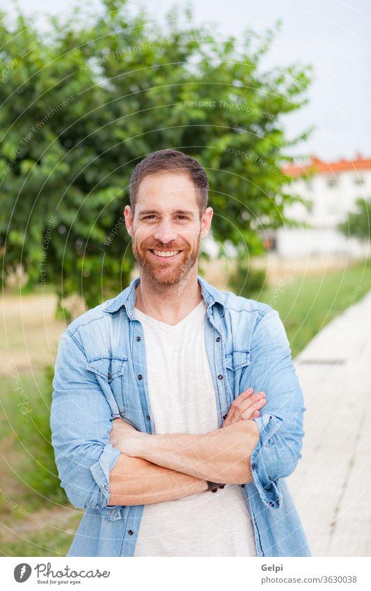 Lässiger Typ entspannt in einem Park männlich jung gutaussehend lässig Mann Model Vollbart Porträt Jeansstoff attraktiv Menschen Erwachsener Person