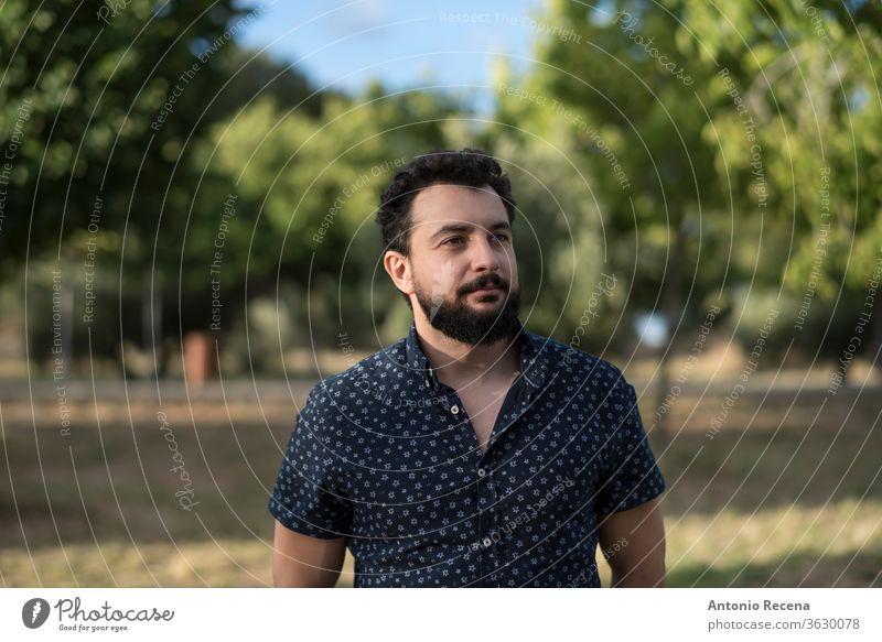 Bärtiger Mann im Freien Portrait bärtig arabisch Spanisch Porträt Menschen echte Menschen Vollbart Lebensstile Person Lächeln Park Hemd lässig Zigeuner Männer