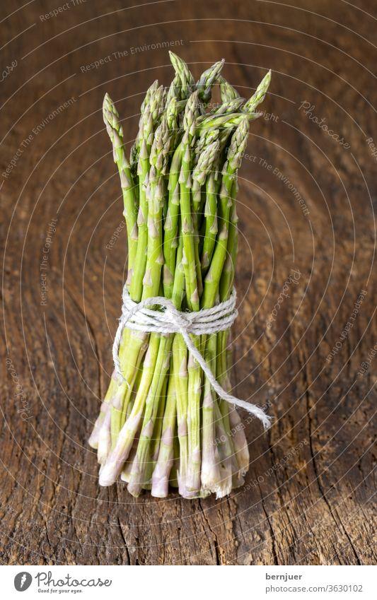 wilder grüner Spargel auf Holz rustikal Bündel Bindfaden Ernährung Lebensmittel Zutat Diät weiß Gemüse frisch Haufen gesund Hintergrund lecker roh Kochen