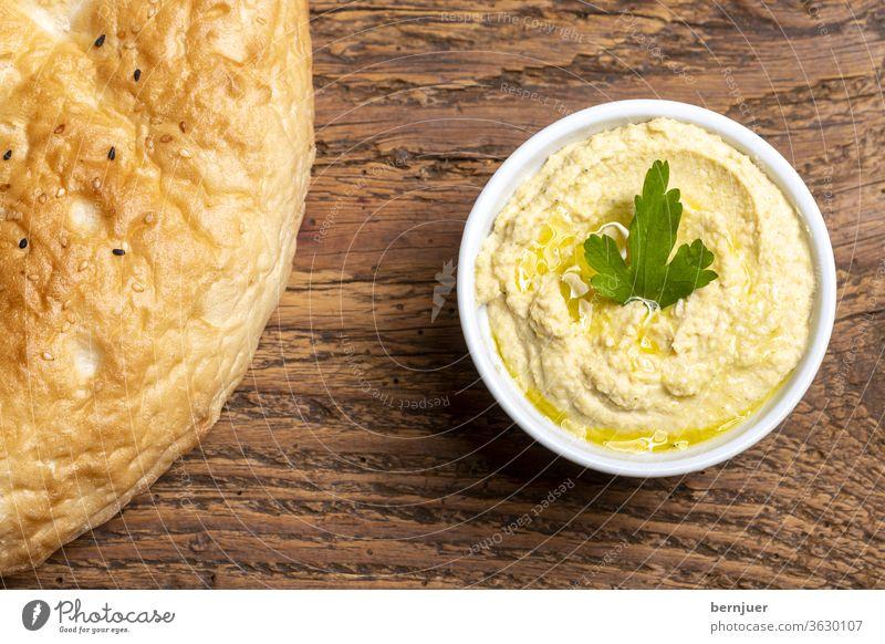 arabischer Humusaufstrich mit Brot Hummus Fladenbrot Aufstrich Sesam Kichererbsen Overhead Kochen Griechisch lecker Gemüse frisch Vorspeise gesund Hintergrund