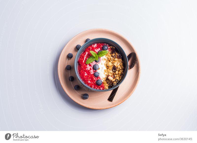 Joghurtschale mit Himbeeren und Granola Smoothie Schalen & Schüsseln Müsli Beeren farbenfroh Farbe Blaubeeren Pastell hölzern Hintergrund Muttern Frühstück