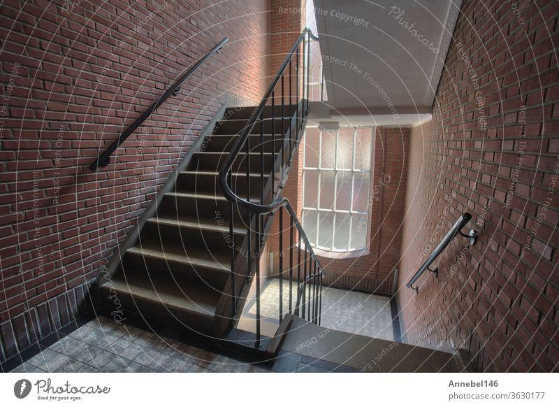 Treppenhaus in Mehrfamilienhaus mit Ziegelmauer, Treppenhaus antiker Gebäudekomplex im alten Stil mit hohen Fenstern Innenbereich Architektur Antiquität Design