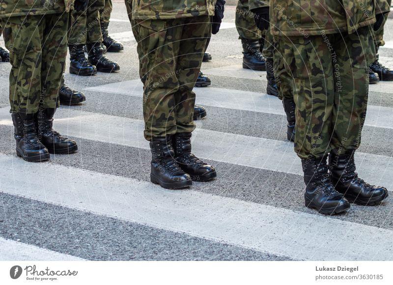 Auf der Straße stehende Soldaten in einer Militäruniform mit Tarnung und schwarzen Militärstiefeln Truppen Springerstiefel Bootcamp Zug Veteranentag Stehen