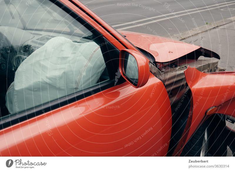 Airbag auf der Beifahrerseite eines roten Autos mit verbeultem Kotflügel Unfall Beule Totalschaden Straße Straßenverkehr Rückspiegel Blech Schaden Versicherung