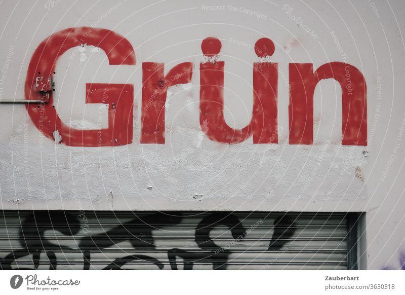 Schriftzug Grün in roten Buchstaben auf grauer Wand mit Jalousie, paradox oder widersprüchlich Widerspruch Paradox rot-grün farbenblind Mauer Fassade Gebäude