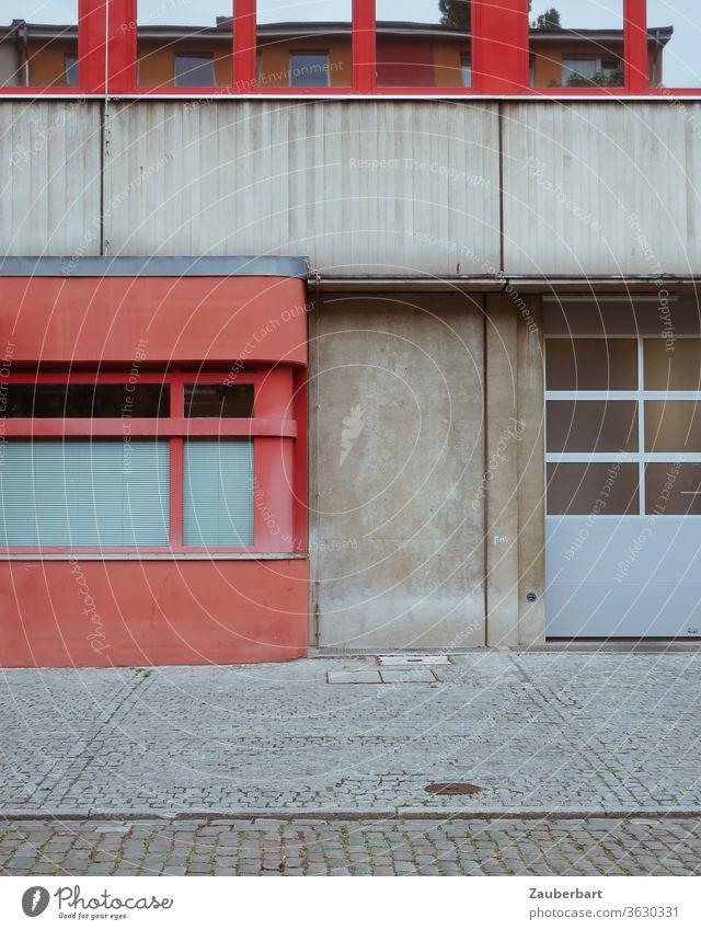 Detail der Fassade eines Feuerwehrgebäudes in Berlin Neukölln in rot und grau Beton Wand Straße Pflaster Tor Fenster Spiegelung geometrisch Segmente 70er Fugen