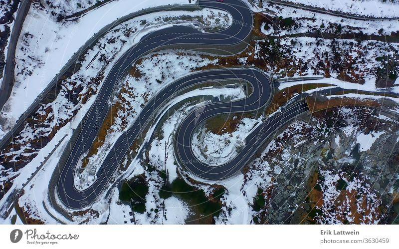 Blick von oben auf eine Passstraße in den Schweizer Bergen bei einem Sieg Schnee Landschaft Winter verschneite Deckung Berge u. Gebirge schön Szene Wald Alp