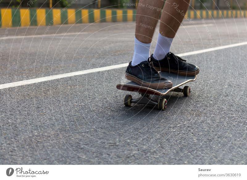 Nahaufnahme der Füße eines jungen Teenagers mit zerrissenen schwarzen Turnschuhen auf seinem Skateboard, der auf einer leeren Straße fährt, während die weiße Linie auf der Straße seine weißen Socken ergänzt und auch als Führungslinie in der Richtung dient, in die er sich bewegt.