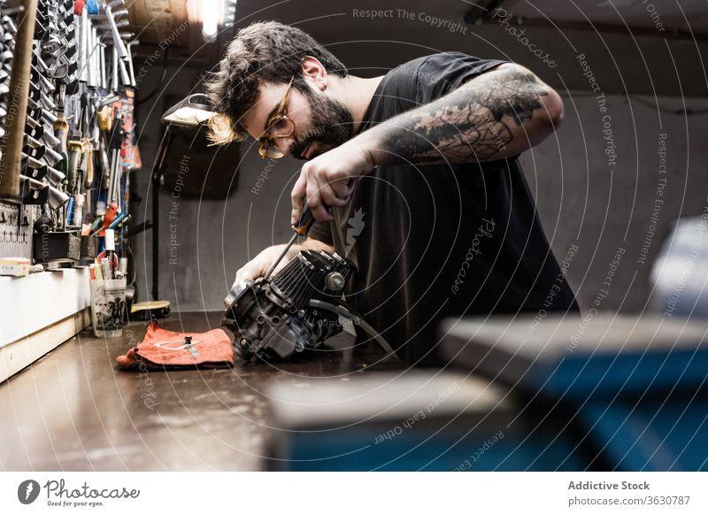 Fokussierter männlicher Mechaniker, der in der Werkstatt arbeitet Reparatur Meister Detailaufnahme Mann Fahrzeug Hobelbank fixieren brutal Seite Arbeit