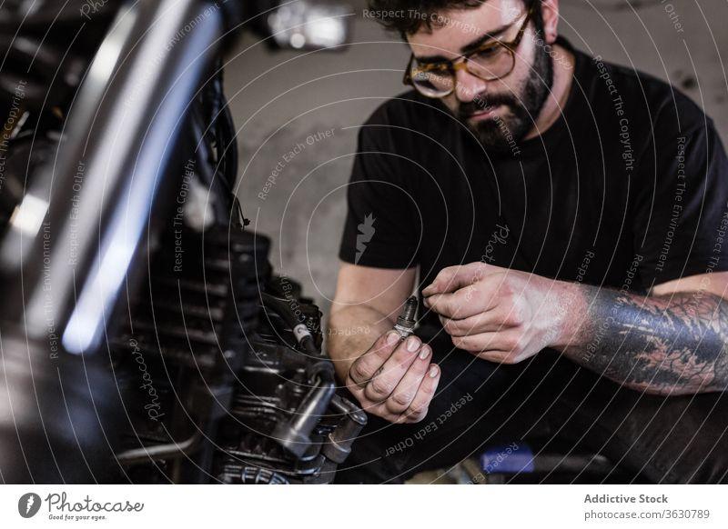 Bärtiger Mann repariert Zündkerze eines Motorrads fixieren Mechaniker Garage dreckig Funken Stecker männlich Reparatur Fahrzeug Werkstatt ernst Flugzeugwartung