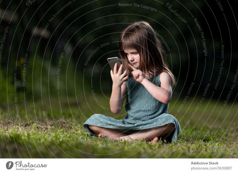 Mädchen surft mit Smartphone im Park erstaunt Schock Überraschung Nachrichten lesen benutzend Rasen Kind Sommer grün Kindheit Kälte Wiese expressiv Unglaube