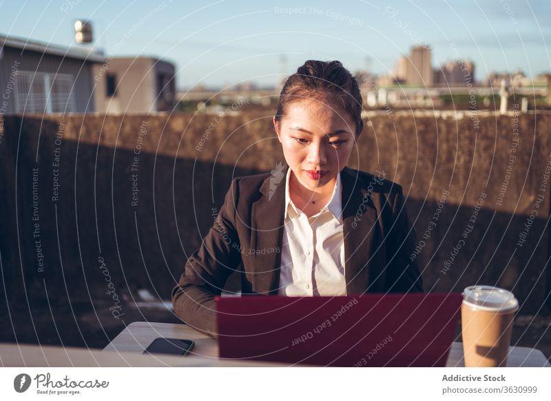 Geschäftige Frau mit Laptop arbeitet auf dem Dach Arbeit benutzend Geschäftsfrau formal Dachterrasse Gerät Apparatur Business asiatisch jung Internet
