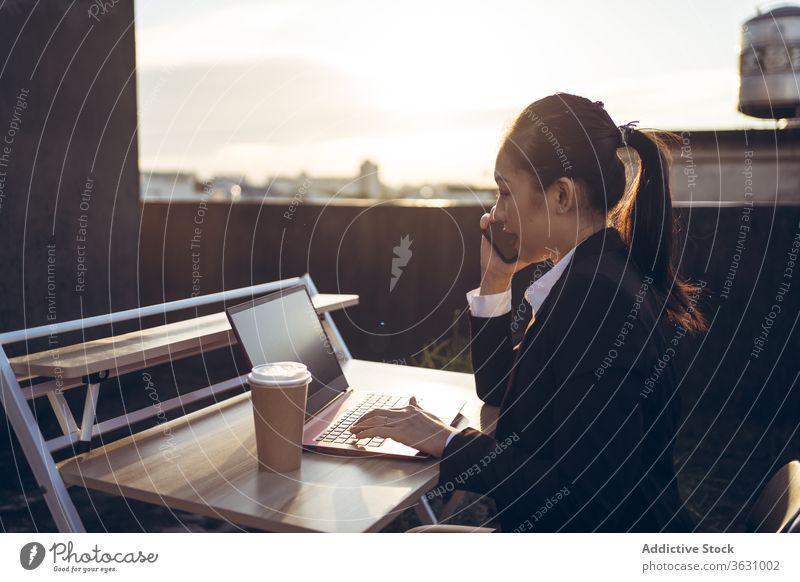Geschäftige Frau mit Laptop arbeitet auf dem Dach Arbeit Smartphone benutzend reden Geschäftsfrau formal Dachterrasse Gerät Apparatur Business asiatisch jung