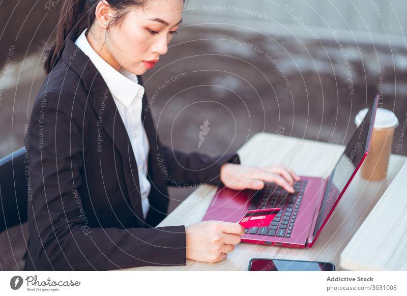 Junge Geschäftsfrau, die mit Kreditkarte und Laptop bezahlt Frau benutzend beschäftigt Smartphone bezahlen online formal jung asiatisch ethnisch ernst Apparatur