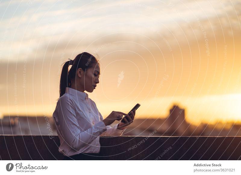 Junge beschäftigte Frau benutzt Smartphone auf dem Dach Geschäftsfrau benutzend ernst Fokus Nachricht Browsen jung asiatisch ethnisch formal Dachterrasse Gerät