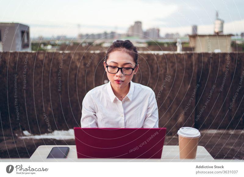 Geschäftige Frau mit Laptop arbeitet auf dem Dach Arbeit benutzend Geschäftsfrau formal Dachterrasse Gerät Apparatur Brille Business asiatisch jung Internet
