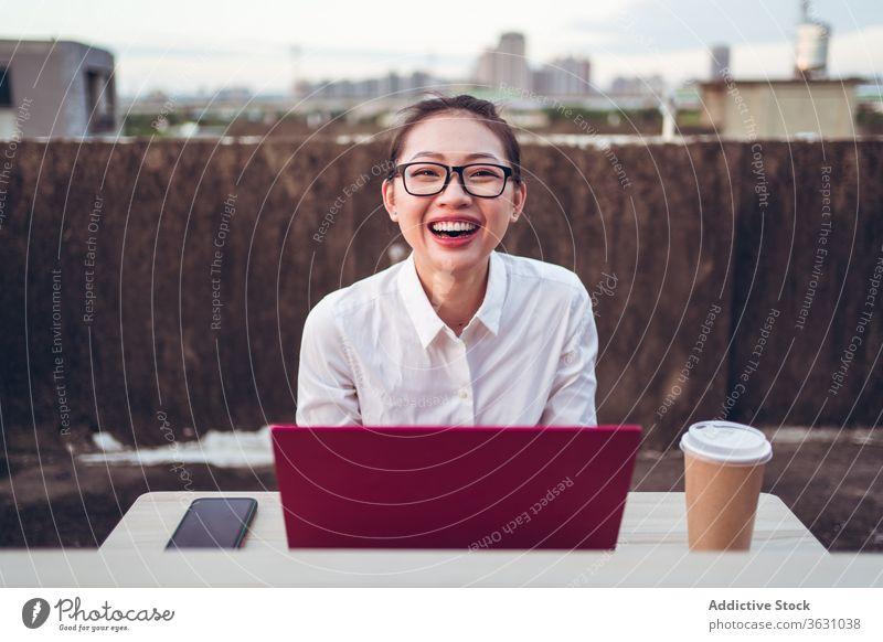 Geschäftige Frau mit Laptop arbeitet auf dem Dach Arbeit benutzend Geschäftsfrau formal Dachterrasse Gerät Apparatur Brille Glück Business asiatisch jung
