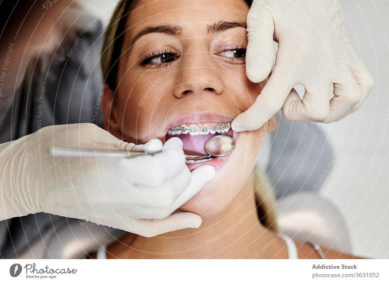 Zahnarzt prüft Zähne des Patienten Frauen geduldig untersuchen Klinik Spiegel Klammer Handschuh Mund geöffnet Arbeit professionell prüfen Zeitgenosse mündlich