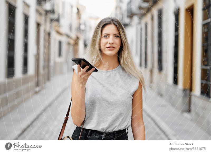 Positive junge Frau mit Smartphone geht auf der Straße Großstadt benutzend Glück Stil Nachricht Spaziergang Browsen Mobile Telefon Lifestyle Gerät Apparatur