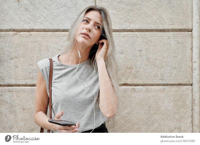 Frau mit Smartphone auf der Straße stehend zuhören Großstadt benutzend jung Glück Stil Nachricht Browsen Handy Lifestyle Gerät Apparatur Musik urban Lächeln