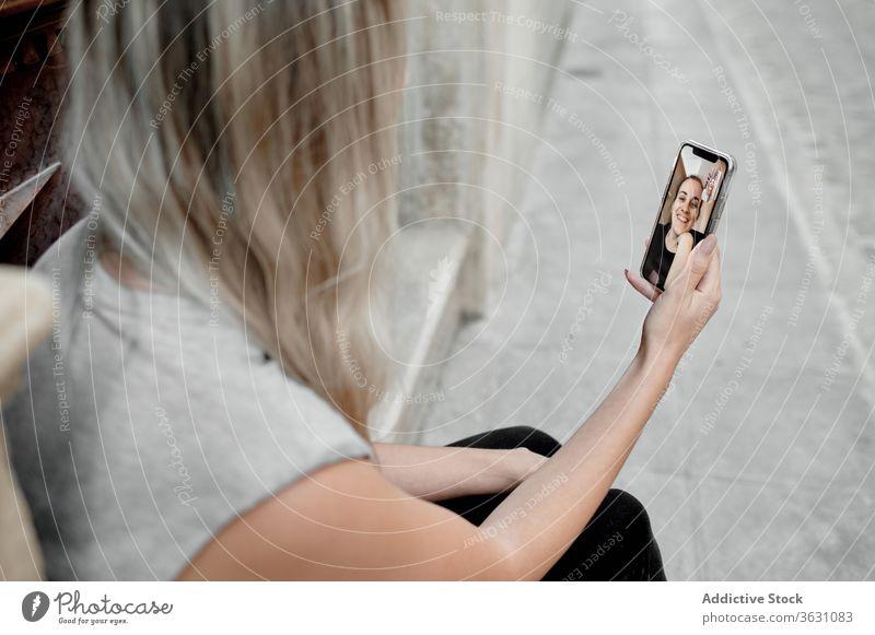 Anonyme Frau mit Videoanruf auf Smartphone auf der Straße Video-Chat Gespräch Mobile Anschluss Apparatur benutzend Freund jung Gerät Kommunizieren Lifestyle