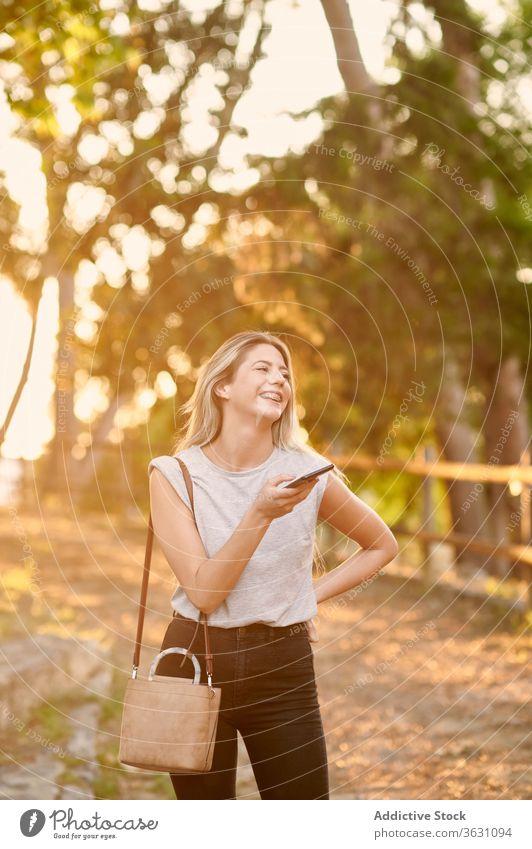 Glückliche Frau mit Smartphone im Park stehend heiter benutzend genießen Browsen jung trendy Lifestyle Apparatur Gerät ruhen Kälte positiv soziale Netzwerke