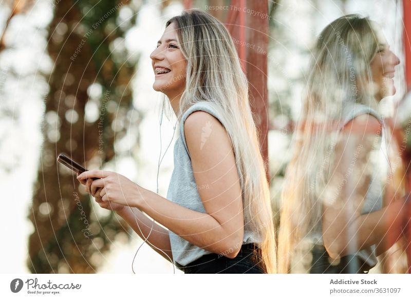 Fröhliche Frau mit Kopfhörern mit Smartphone auf der Straße Glück heiter zuhören benutzend Browsen jung Musik genießen Gerät Apparatur Lifestyle Lächeln online