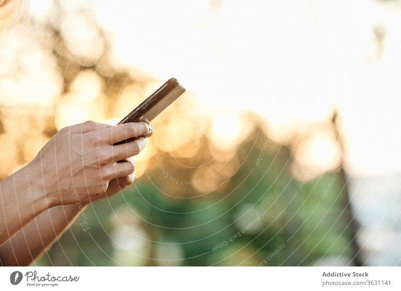 Anonyme Frau mit Smartphone im Park stehend benutzend genießen Browsen jung trendy Lifestyle Apparatur Gerät Kälte positiv soziale Netzwerke Lächeln online