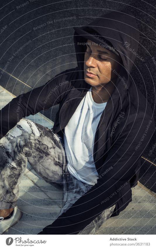 Stilvoller Mann in trendigem Outfit auf der Straße Mode trendy Straßenbelag Gebäude urban Großstadt modern männlich ethnisch sitzen jung Wand fettarm