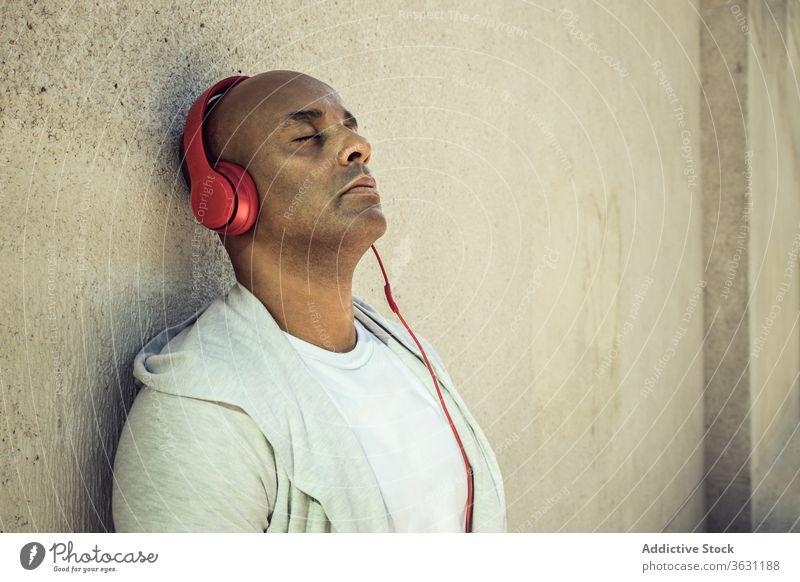 Entspannter Mann hört Musik über Kopfhörer genießen zuhören friedlich sich[Akk] entspannen Harmonie Gesang Großstadt männlich ethnisch Klang Kälte Gerät fettarm