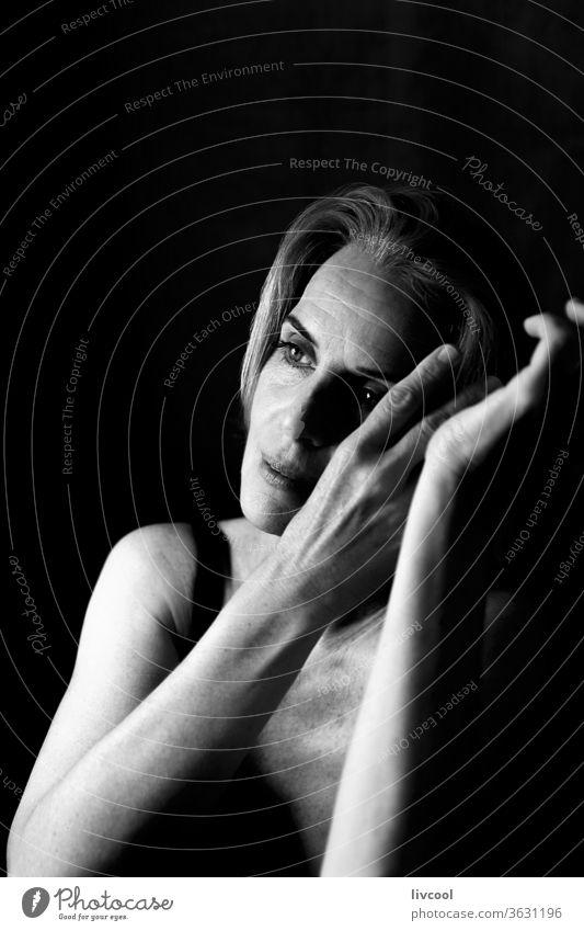 Frau in einer nachdenklichen und romantischen Haltung zwischen Licht und Schatten Porträt Menschen Einstellung Licht & Schatten schwarz auf weiß eine Person