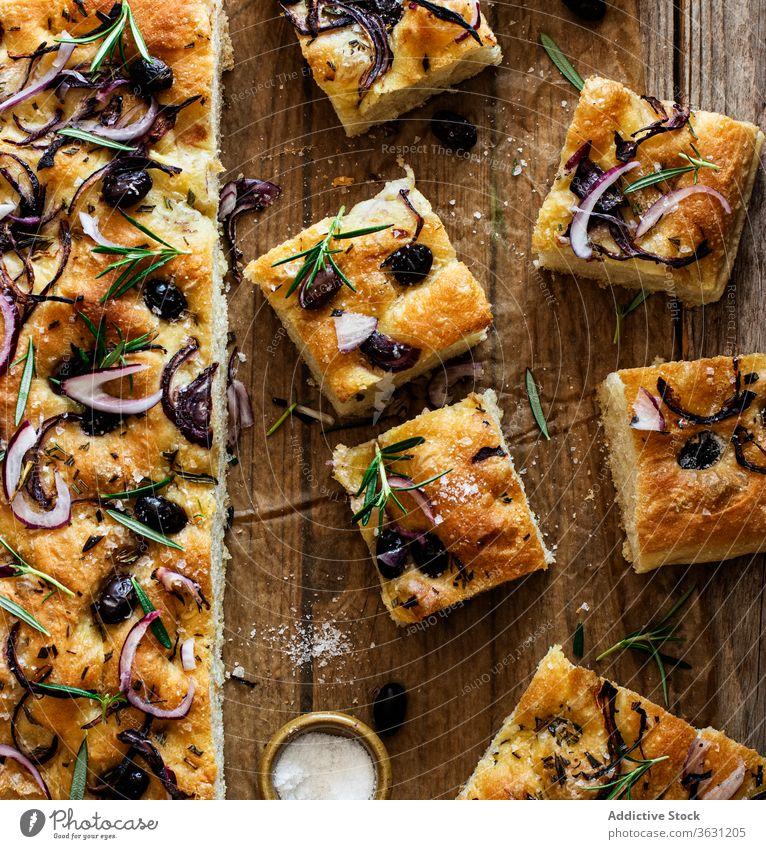 Focaccia mit schwarzen Oliven und Kräutern auf Holztisch hölzern Brot Hefe oliv italienisches Brot Focaccia-Brot Bestandteil handgefertigt Zwiebeln