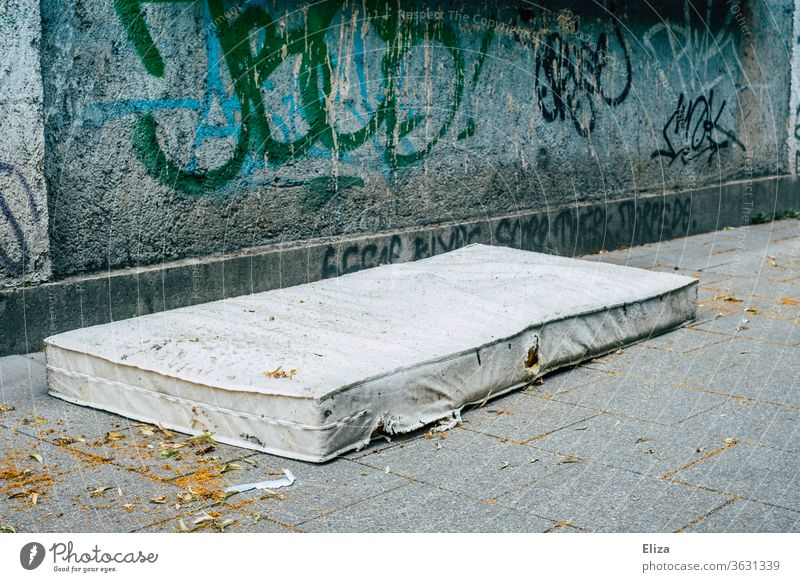 Eine alte Matratze auf der Straße vor Graffiti. Konzept Wohnungsnot und Obdachlosigkeit. Wohnungssuche draußen schlafen Verzweiflung Armut Schlafplatz obdachlos