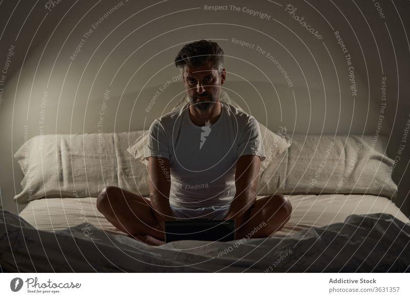 Mann benutzt Laptop im Schlafzimmer heimwärts Bett Browsen benutzend positiv Lächeln reif Sitzen ruhen männlich lässig Gerät Apparatur sich[Akk] entspannen