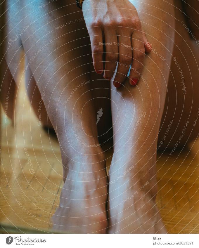 Spiegelbild zweier Frauenbeine und eine Hand mit rotem Nagellack im Spiegel Beine weiblich feminin lackierte Fingernägel Haut sinnlich sitzen nackt Mensch