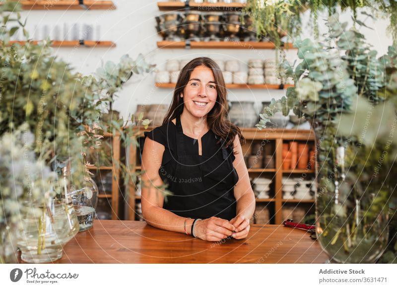 Positiver Eigentümer der Floristikwerkstatt schaut in die Kamera Frau geblümt Besitzer Blumenhändler Glück Erfolg positiv selbstbewusst Werkstatt Pflanze