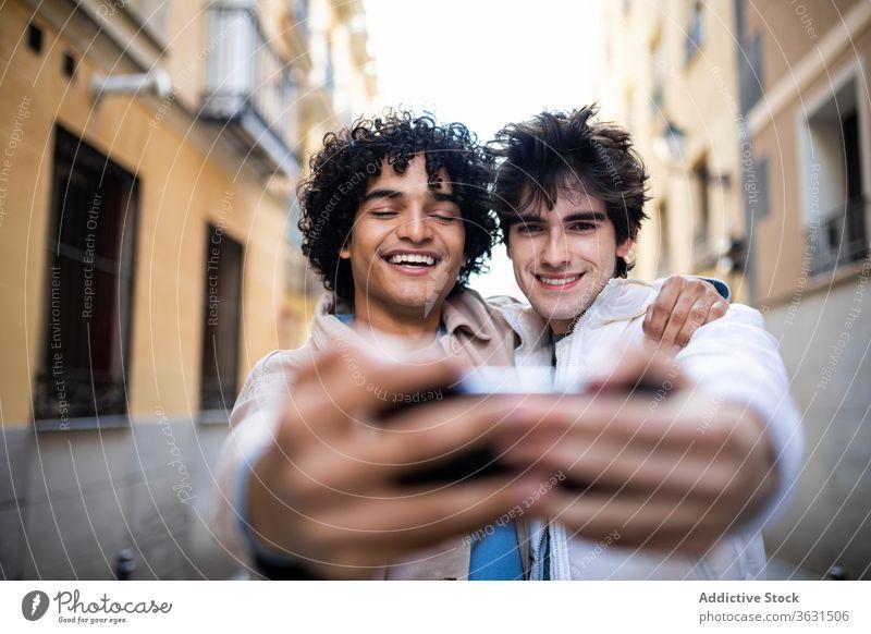 Fröhliches homosexuelles Paar nimmt Selbstliebe am Smartphone Homosexualität Selfie Umarmung schwul Zusammensein Straße lgbt Handy benutzend rassenübergreifend