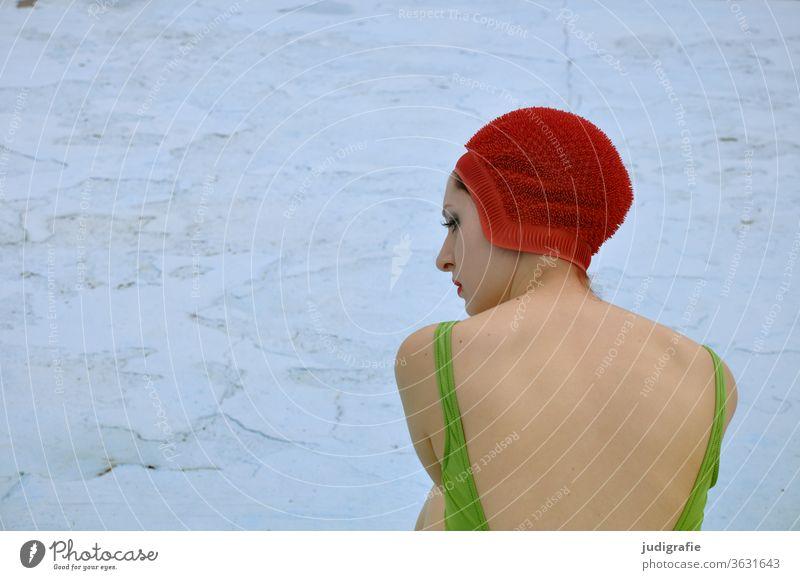 Das Mädchen mit der schönen roten Badekappe und grünem Badeanzug sitzt im leeren Nichtschwimmerbecken. Eine Sommerliebe. Frau Badebekleidung Badehaube Haut jung