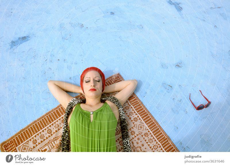 Das Mädchen mit der schönen roten Badekappe und grünem Badeanzug sonnt sich im leeren Nichtschwimmerbecken. Eine Sommerliebe. Frau Badebekleidung Badehaube Haut