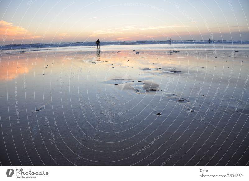 Weiter nasser Strand im Schimmer des Sonnenuntergangs. Wellen, Wolken und Menschen in der Ferne. Abenddämmerung Strandspaziergänger Sportler Surfer Bodyboard