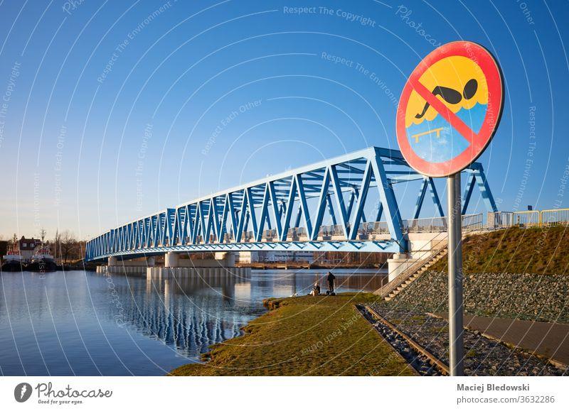 Kein Badeschild an der Oder bei Sonnenuntergang in Szczecin (Stettin), Polen. kein Schwimmen Zeichen Fluss Großstadt Brücke Wasser Gefahr Ermahnung Himmel blau