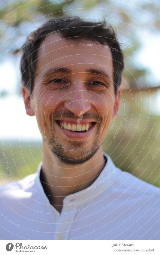 Junger Mann im weißen Hemd lacht Männergesicht Porträt weißes hemd Natur natürlich Bewerbung motiviert fröhlich Bart dunkelhaarig Lichterscheinung