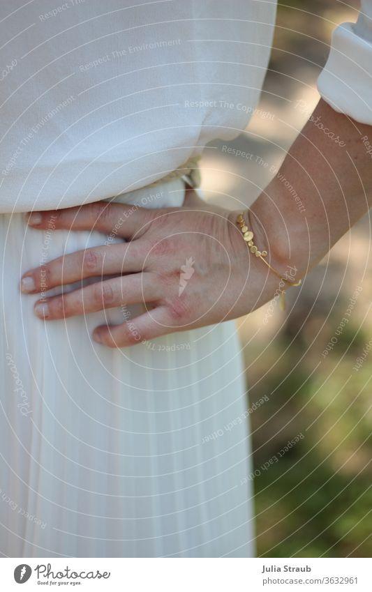 Hand mit goldenem Armreif Braut Hochzeit Finger plissee falten Faltenrock Seide seiden weiß Creme Bluse Sommer Natur