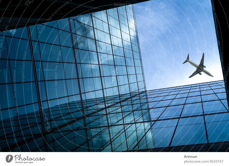 Flugzeug fliegt über einem modernen gläsernen Bürogebäude. Perspektivische Ansicht eines futuristischen Glasgebäudes. Außenansicht des gläsernen Bürogebäudes. Geschäftsreise. Spiegelung in transparentem Glas. Fenster eines Unternehmens.
