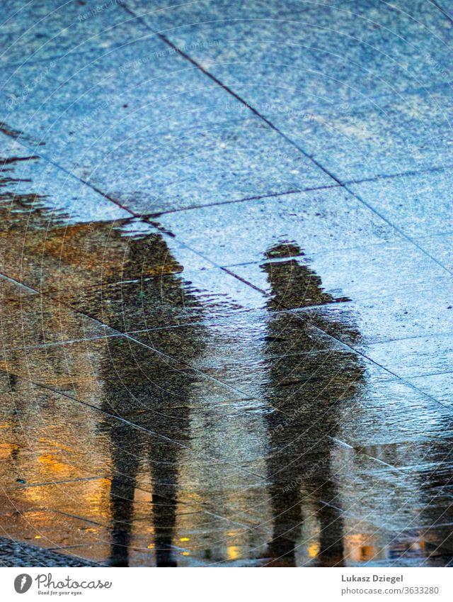 Silhouetten von Menschen, die sich auf den regennassen Bürgersteigen spiegeln Kunst Form kreativ verschwommen deprimiert Oberfläche Boden Stimmung Leben