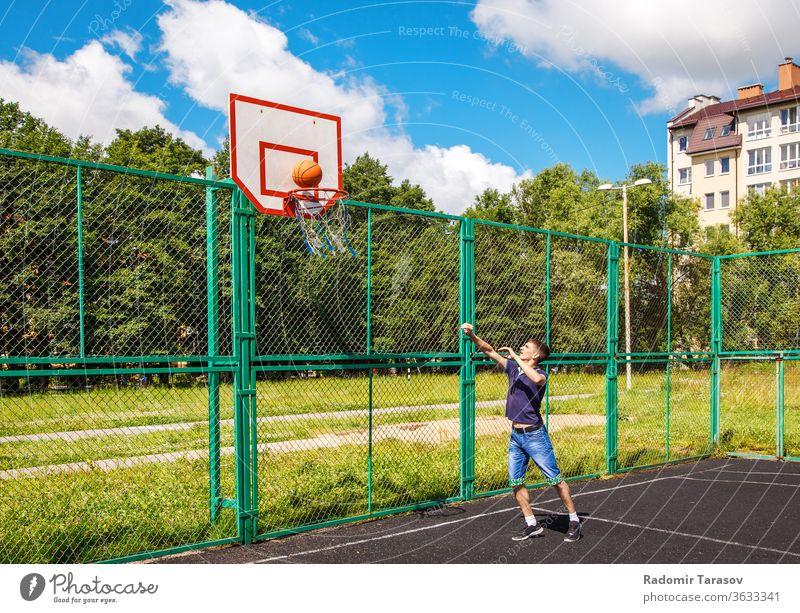 junger Mann, der an einem sonnigen Sommertag im Freien Basketball spielt Straße Menschen urban Großstadt Person Erwachsener Lifestyle Glück männlich Freizeit