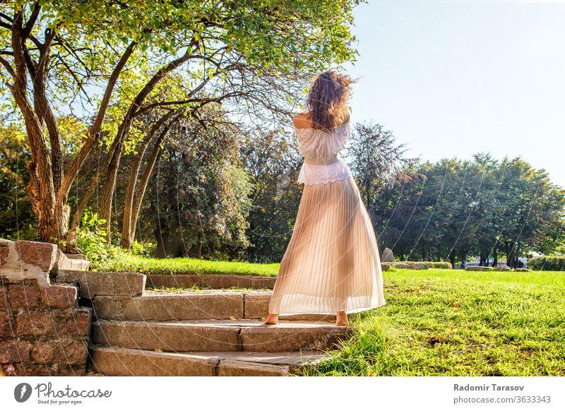 junges Mädchen in leichtem Kleid, das an einem sonnigen Sommertag mit dem Rücken im Park steht Licht Frau Schönheit Natur Lifestyle im Freien schön Person