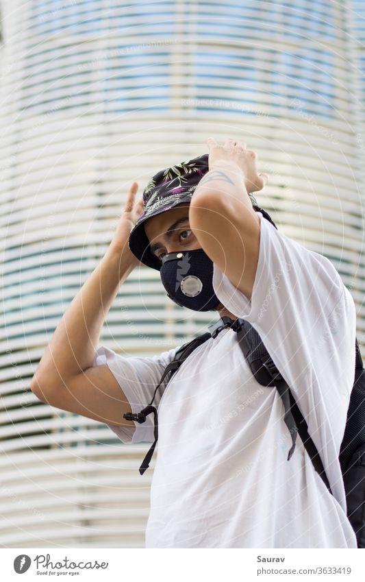 Ein junger Mann im Freien mit einer schützenden Gesichtsmaske zur Verhinderung einer Coronavirusinfektion, der während einer globalen Pandemie seine blumig bedruckte Eimerkappe anpasst und einen Beutelpack trägt.